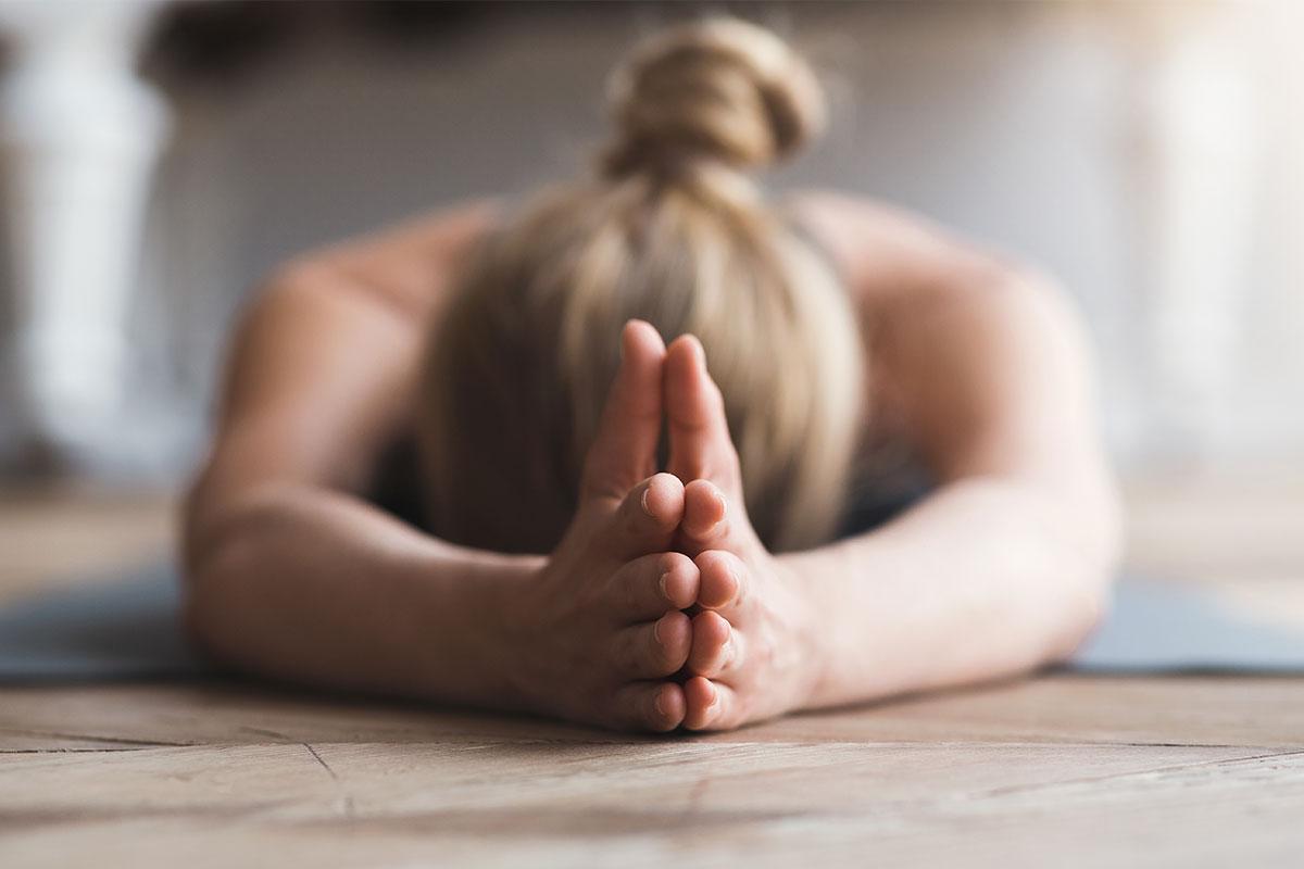 Chica practicando yoga por la mañana